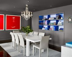 Matte gray walls, a clean-lined dining table and sleek dining chairs create a modern aesthetic in this dining room. Striking red artwork and blue-lighted shelves add bold bursts of color to the space, and a traditional chandelier adds an unexpected touch of elegance.