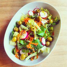 Ensalada de lechuga, rabanillos, pepino, zanahoria, aceitunas y semillas de sésamo