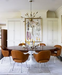 Mid-century modern dinning room with leather brown chairs, large framed art, and gold chandelier