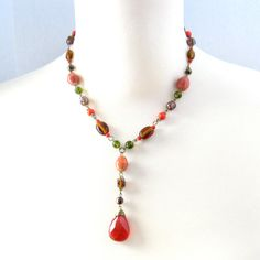 Fabulous beaded chain deco lavaliere necklace with wonderful autuminal color hues of orange, terra cotta, red, bronze, avocado green and amber, The chain is bronze tone metal and the beads are glass and ceramic.  The beaded chain has a mixture of colors, shapes, and sizes of these glass and ceramic beads to create a lovely airy, textured look in these beautiful colors.  CONDITION: The necklace is in mint condition, everything is connected well. Beads are intact and clasps work well. Looks…