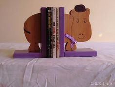 This is a hand-crafted wooden book end that looks like a hippo. The shape is made of a single piece of wood and has been stained and varnished. The base is painted and polyurethaned. The detail has been added by hand with a wood burning tool,and is only on one side. Dimensions: