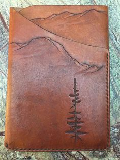 ThIs is one of a kind leather iPad Mini Sleeve. I have designed and carved/stamped by hand a mountain scene into the leather. The leather was hand stitched. The vegetable tanned leather was then dyed and treated. Finally sealed to preserve and repel moisture. The edges have also been treated and polished. 1/8 inch vegetable tanned leather Mountain and tree scene design
