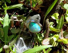 This exquisite RING features a stunning Boulder OPAL, with a 24-carat yellow GOLD setting on the front that holds the beautiful gemstone. The ring is handcrafted in 925 sterling silver and is rhodium plated. Rhodium plating is used to increase the strength, durability, and bright look of silver with a hammered finish. Opal gemstones are unlike any other thanks to their brilliant and unusual play of color. OPAL: Australian Black Opal is considered the most precious variety and was formed…