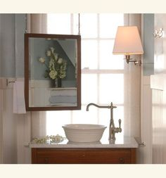 Love this little powder room!  Hanging framed mirror from ceiling off set in front of the window is unique and lovey! Great way to effectively use the space and maintain natural lighting.