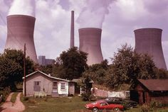 Water cooling towers of the John Amos Power Plant loom over a home located across the Kanawha River, near Poca, West Virginia, in August of 1973.