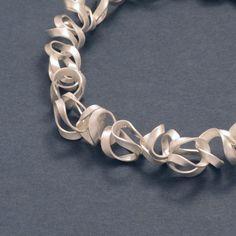 """Diese edle Silberkette wirkt wie unregelmäßig in sich verschlungene Bänder, die an Bandnudeln erinnern. Der Übergang zwischen den Gliedern ist durch das """"Gestrick"""" nicht zu erkennen, wodurch die Kette, wie ein fließendes, verwickeltes Band erscheint."""