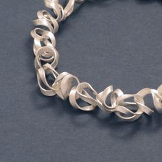 """The transitions between the links are carefully """"knitted"""" and cannot be seen, which causes the chain to look like a flowing and intricate band. This fine silver chain showcases irregularly intertwined bands that resemble fettuccine noodles."""