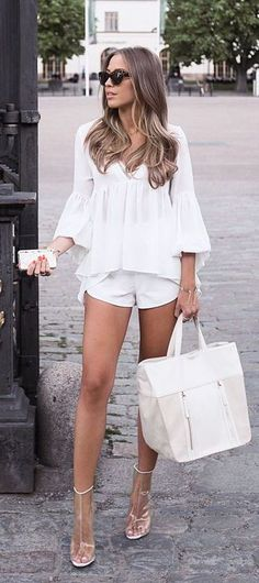 all white summer outfit with a white lace blouse, white shorts, nude heels and white purse