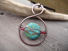 Beautiful pendant necklace wire wrapped and made of solid copper metal. -In a pretty original (by tfuniquetwists) waves design -Featuring a natural composite stone mix bead in turquoise blue - color of the seas in the Caribbean. Red glass beads were added to give it a southwestern