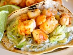 Super Simple Shrimp Tacos with cilantro lime sauce 1 lb of frozen shrimp, defrosted, peeled, & deveined 6 oz fat free Greek yogurt ¼ cup chopped cilantro 2 tbsp fresh lime juice 1/2 tsp cayenne pepper ½ a head of cabbage, thinly sliced (about 5 cups) 8 corn tortillas 4 tsp extra virgin olive oil Salt and pepper to taste