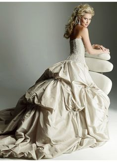 This is a wedding dress designed by Maggie Sottero. The back fullness of this dress is very similar to the bustle period. It was clearly inspired by the wedding and formal dresses of that time, but made white and give a strapless beaded bodice to give it a modern twist. The gathering at the back and the long train are very bustle period elements.