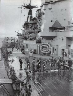 Sailors scrubbing the deck of HMS RODNEY. 16 Royal Navy sailors on HMS RODNEY in fatigues whilst 'alongside'. Together with HMS KING GEORGE V she accounted for the crippled BISMARCK in May 1941.