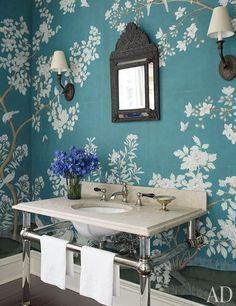 A Gracie wallpaper transforms the powder room into a garden; the basin and pedestal are by Urban Archaeology, and the sink fittings are by Waterworks.