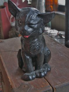 A rare Victorian Bretby redware pottery black cat c.1900 with one eye squinched shut, tongue hanging out and a ragged looking ear. The open