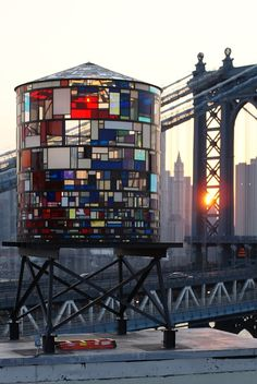 "Watertower at 20 Jay Street, Brooklyn.  artist Tom Fruin flipped the switch on his latest installation, a replica of the iconic New York rooftop structure made from 1000 pieces of salvaged plexiglass. Fruin collected the colorful pieces from all over NYC, ""from the floors of Chinatown sign shops to the closed Dumbo studio of Artist Dennis Oppenheim to Astoria's demolition salvage warehouse."