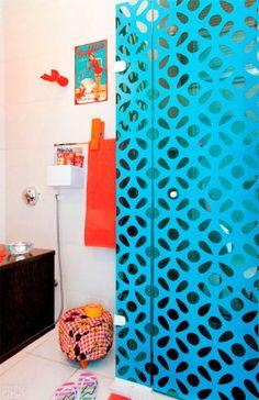 A publicitária e blogueira carioca Vivi Visetin adora o visual dos elementos vazados conhecidos como cobogós e quis inseri-los na decoração do seu banheiro: para isso recortou adesivos vinílicos azuis no formato do seu bloco preferido e colou-os no boxe de vidro transparente.