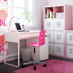Un despacho doméstico con un escritorio blanco, una estantería rosa con cajas blancas y una silla giratoria rosa