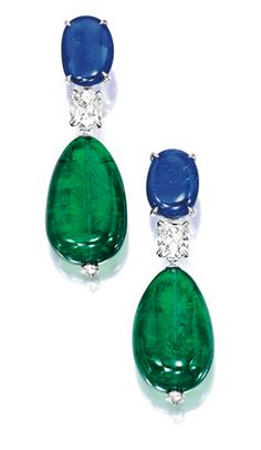 Pair of Emerald, Sapphire and Diamond Earrings:  Each suspending an oblong emerald bead, to a surmount set with a cabochon sapphire, connected by a cushion-shaped diamond weighing 1.03 and 1.02 carats respectively, the emeralds and sapphires altogether weighing approximately 52.00 and 12.00 carats respectively, mounted in 18 karat white gold.