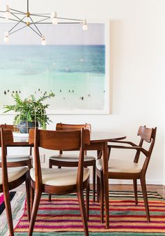 """HGTV star Emily Henderson made over DesignLoveFest blogger Bri Emery's home. In the dining room, Max Wagner's """"Tulum"""" photo hangs on the wall behind the dining set, purchased at Mid-Century LA. The amazing light fixture is by Brendan Ravenhill, and the layered kilims add lots of color."""