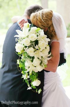 Wedding couple first embrace, white cascading bouquet  Photography: www.DelightPhotography.com