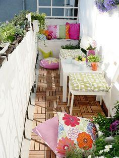 Joli balcon aménagé avec une terrasse de bois petites tables et coussins colorés