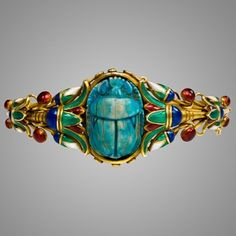 An antique gold and enamel scarab bracelet in the Egyptian Revival style with multicolored enamel lotus leaves centering on a blue faience scarab, in 18k. Marcus Co. United States.