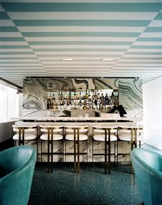 White-and-brass bar stools and a marble bar paired with striped ceilings