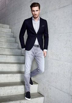 Pairing a navy blue blazer with grey jeans is an on-point option for a day in the office. Black low top sneakers will contrast beautifully against the rest of the look.   Shop this look on Lookastic: https://lookastic.com/men/looks/blazer-long-sleeve-shirt-jeans/18721   — Grey Long Sleeve Shirt  — Navy Pocket Square  — Navy Blazer  — Grey Jeans  — Black Low Top Sneakers