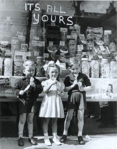 Some rather neatly dressed kiddie-winks tuck into the first unrationed sweeties they'd ever have tasted  - 1953.