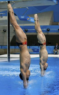 Gold medalists in the Men's Synchronized 3m Springboard final  China's Luo Yutong (L) and Qin Kai enter the water after performing a dive.