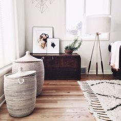 Pinterest: tobieornottobie boho living room with white woven baskets, wood floors, dark dresser, standing modern lamp with gold