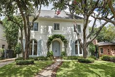 Massive Curb Appeal with a beautiful white brick exterior and french blue shutters to match the front door.  slightly winding front walkway with brick border adds charm and appeal