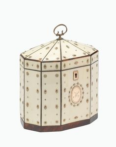 A GEORGE III GOLD, IVORY AND TORTOISESHELL TEA CADDY, LATE 18TH CENTURY -  octagonal, the ivory panels applied with rows of gold beads and pellets between tortoiseshell stringing, a tortoiseshell band to the base, applied to the front with a bright-cut bordered gold oval initialled H below the gold key escutcheon, the lid rising to a silver loop hinged handle, foiled interior 13cm wide