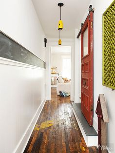 Add a rustic, farmhouse look to your home with this idea for using a distressed barn-door for a pop of color and reclaimed wood floors to add the finished rustic look.