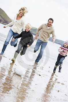 Family playing soccer at beach smiling by Monkey Business Images, via Dreamstime