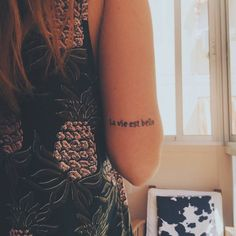 "Little tricep tattoo saying ""La vie est belle"", french phrase which means ""Life is beautiful""."