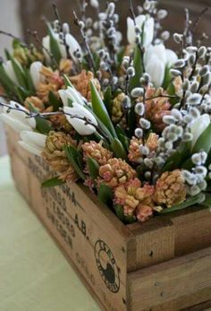 Hyacinth, tulips and pussy willow displayed in a wooden box.