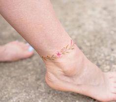 Motif incontournable dans l'histoire de l'inkage, la fleur est une superbe idée de tatouage cheville plein de douceur et de romantisme.
