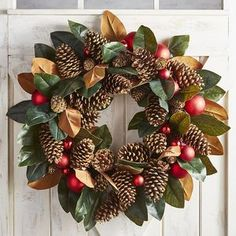 Exclusively handcrafted for Pier 1, our stunning oversized faux magnolia wreath offers a colorful, confident greeting to guests and family alike. Natural pinecones are nestled among faux magnolia leaves and deep crimson ornaments, resulting in a lush, Southern-inspired piece of art. It's perfect for mantels and doors or laid flat as a centerpiece.