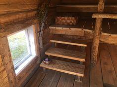 Savusaunan portaat ja pieni alaosassa sijaitseva ikkuna, joka tuo valoa sisälle