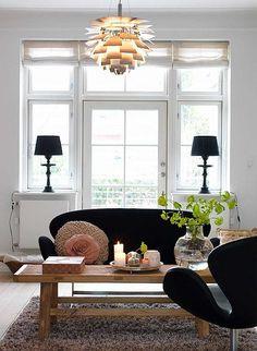 a danish family home by the style files, via Flickr - white living room, black sofa, artichoke light