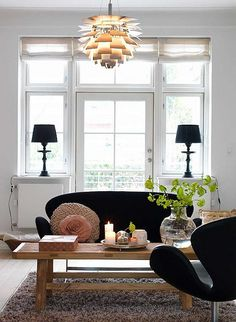 a danish family home by the style files, via Flickr - white living room, black sofa, artichoke light