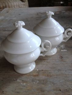 Matched pair of 1800's cream pots w/covers.Pure white porcelain and delicately curved handles make these exceptionally lovely.  Add to it that they have their original lids with flower detail knob and they are a dream.Excellent condition.  2.75