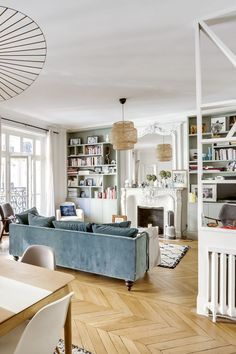 Home Decor Tips Parisian Apartment Decor Guide - faded blue sofa in parisian living room with marble fireplace and herringbone parquet floors via CoteMaison Studio 85 By Casaromani et Conscience Parisian Bedroom, Parisian Decor, Parisian Style, Cozy Bedroom, Home Living Room, Living Room Decor, French Living Rooms, Studio Living, Dining Room