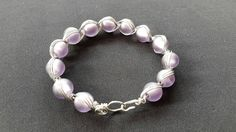 Check out this item in my Etsy shop https://www.etsy.com/uk/listing/268380120/violet-lilac-bead-and-wire-bracelet