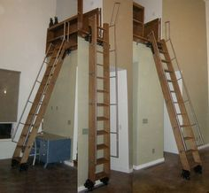 This loft ladder can rest at an angle to climb into the loft or can be pushed upright to be used as a sliding library ladder. Might be the best option.