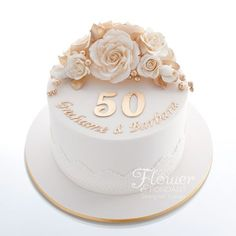 Single tier ivory & gold 50th Anniversary cake. Adorned with ivory & gold sugar roses and trimmed with edible lace.