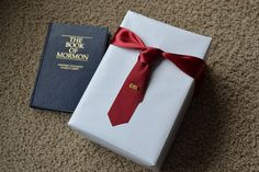 LDS first set of scriptures wrapped in white for boy's baptism gift. Use a satin ribbon and wrap on package like a tie. I added a CTR tie tack for embellishment as an extra added gift.