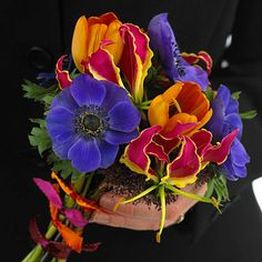 Handheld posies like this are popular alternatives to pin-on corsages, which have a tendency to sag when pinned on flimsy or silk material. Purple anemones, orange tulips, and gloriosa lilies are the stars of this petite bouquet. Note the coordinating ribbon wrap on the stems. --Photographer Scott Little; Floral designer Dan Brabec/