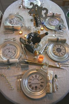 A unique New Year's Eve dinner table setting using silver chargers, clock faces…